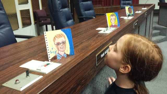 Ella checks out Lucy's portraits, in preparation for delivering her testimony.